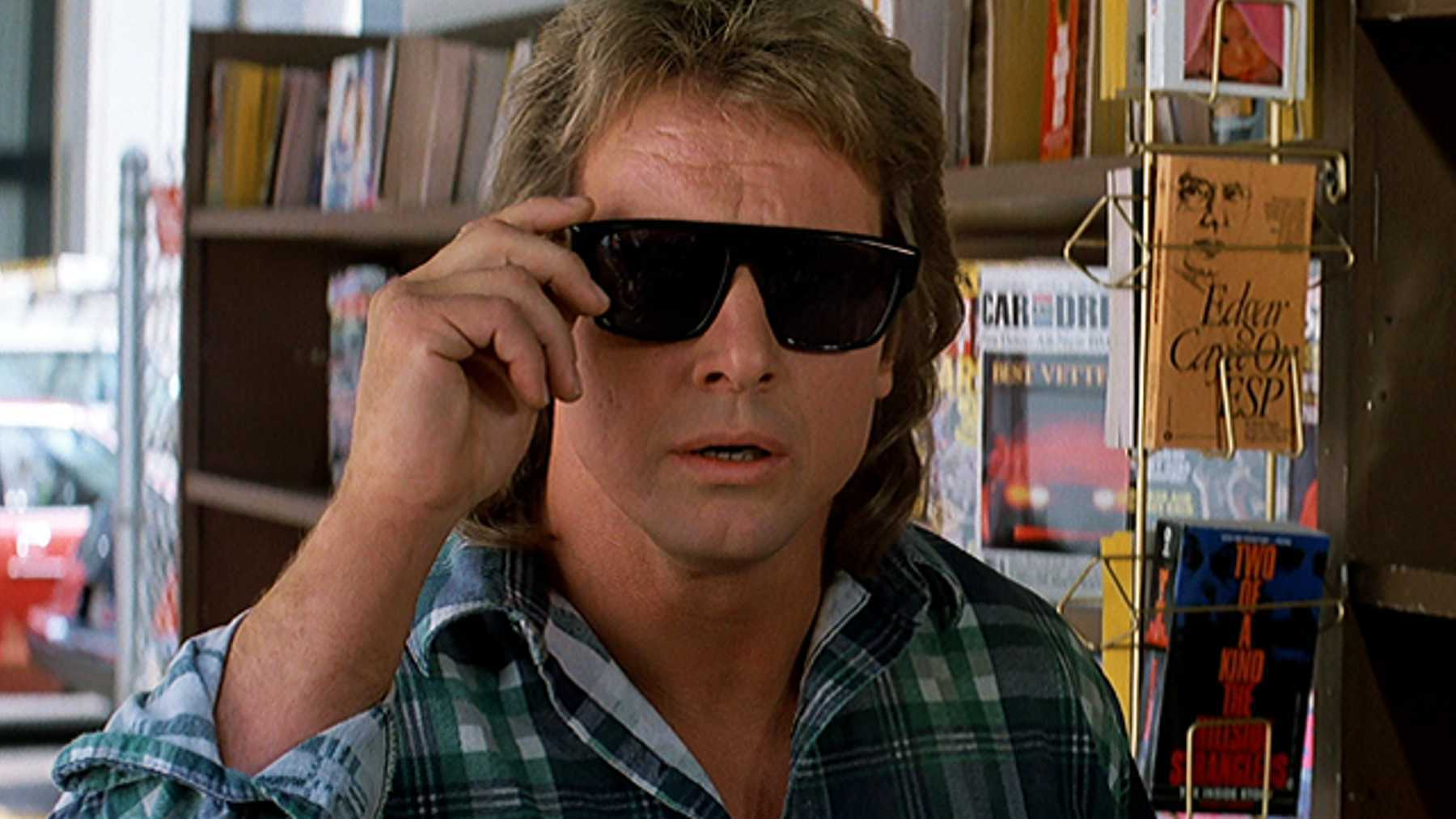 A meme of Rowdy Roddy Piper, wearing sunglasses in the movie They Live.