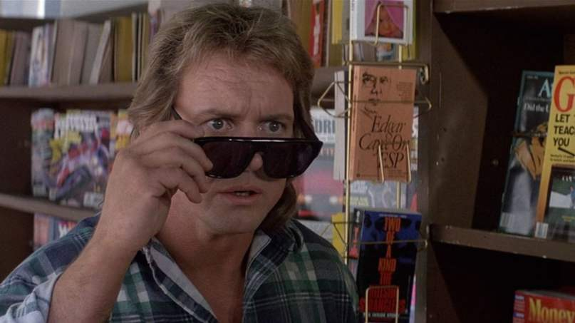 A meme of Rowdy Roddy Piper, removing his sunglasses to get a look at something, in the movie They Live.
